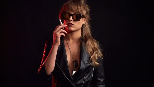 Porträt einer eleganten blonden Frau mit Brille, die im Studio eine Zigarette auf schwarzem Hintergrund raucht
