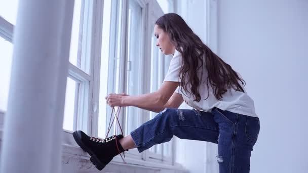 Portrét krásné sexy bruneta žena na sobě džíny a tričko pózuje v bílém studio
