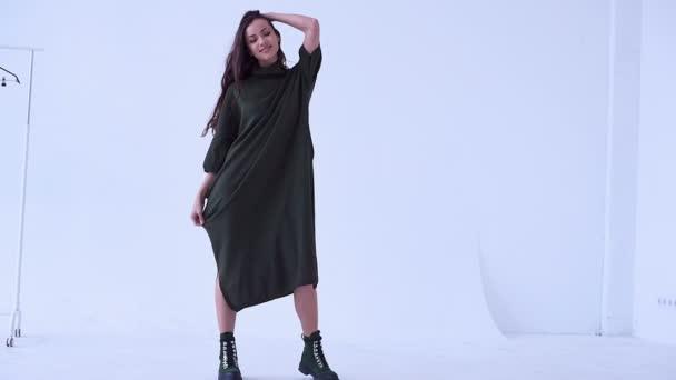Portrét krásné sexy bruneta žena nosí dlouhé zelené šaty pózuje v bílém studio