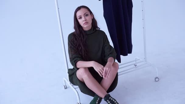 Portrait of beautiful glamor brunette woman wearing long green dress posing in white studio