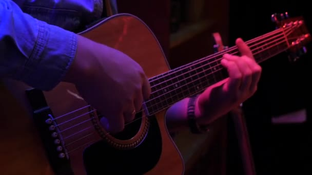 A zenész gyönyörű akusztikus gitáron játszik a színpadon..