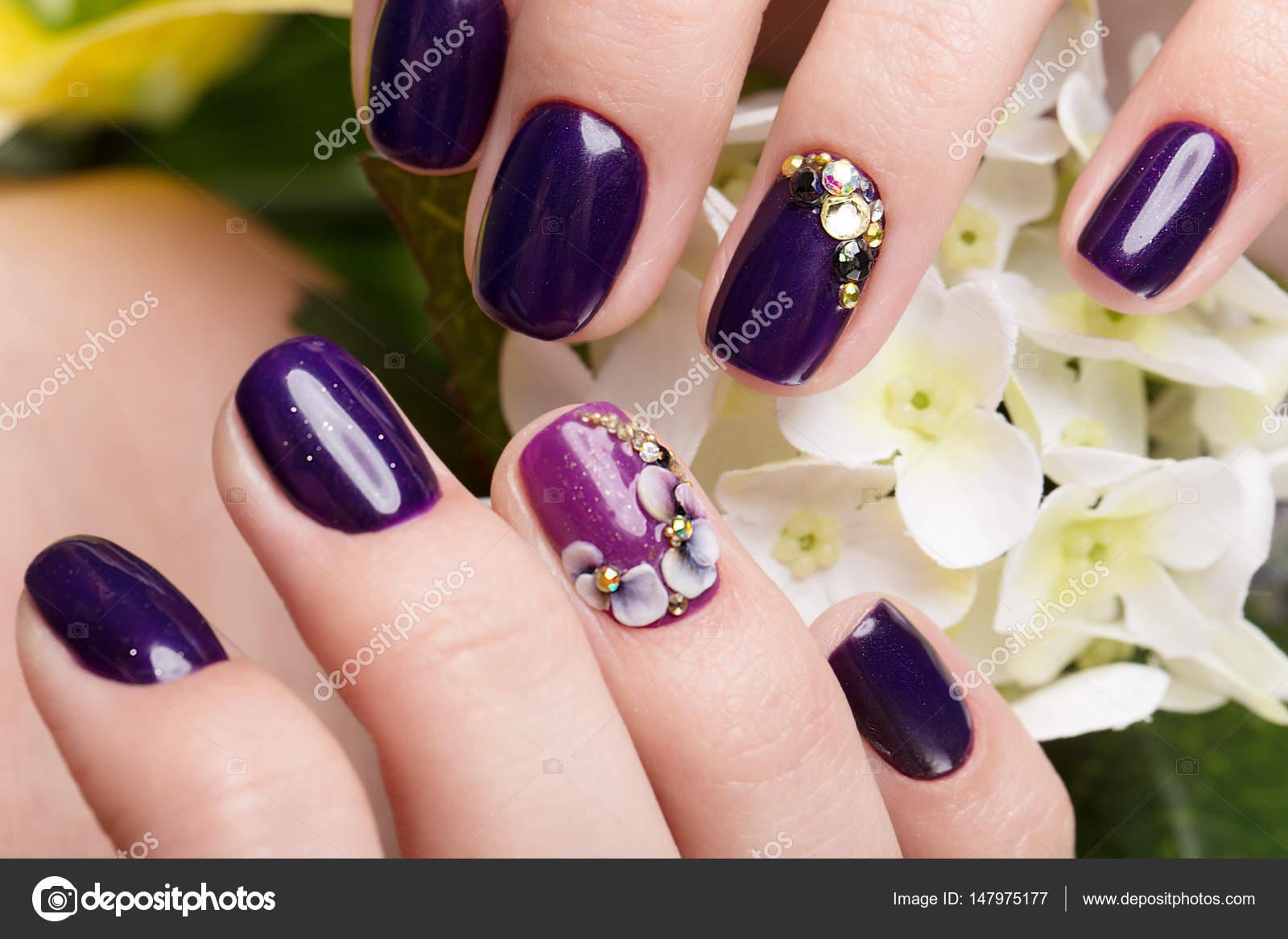 Schöne Maniküre mit Blumen auf weibliche Finger gedreht. Nägel ...