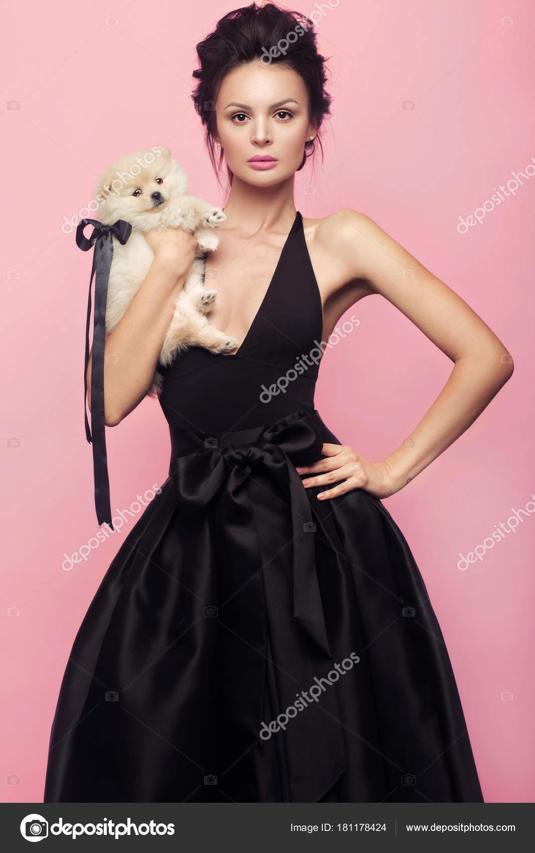 Mode-schöne Frau im schwarzen Kleid mit Schleife, Retro-Make-up und ...