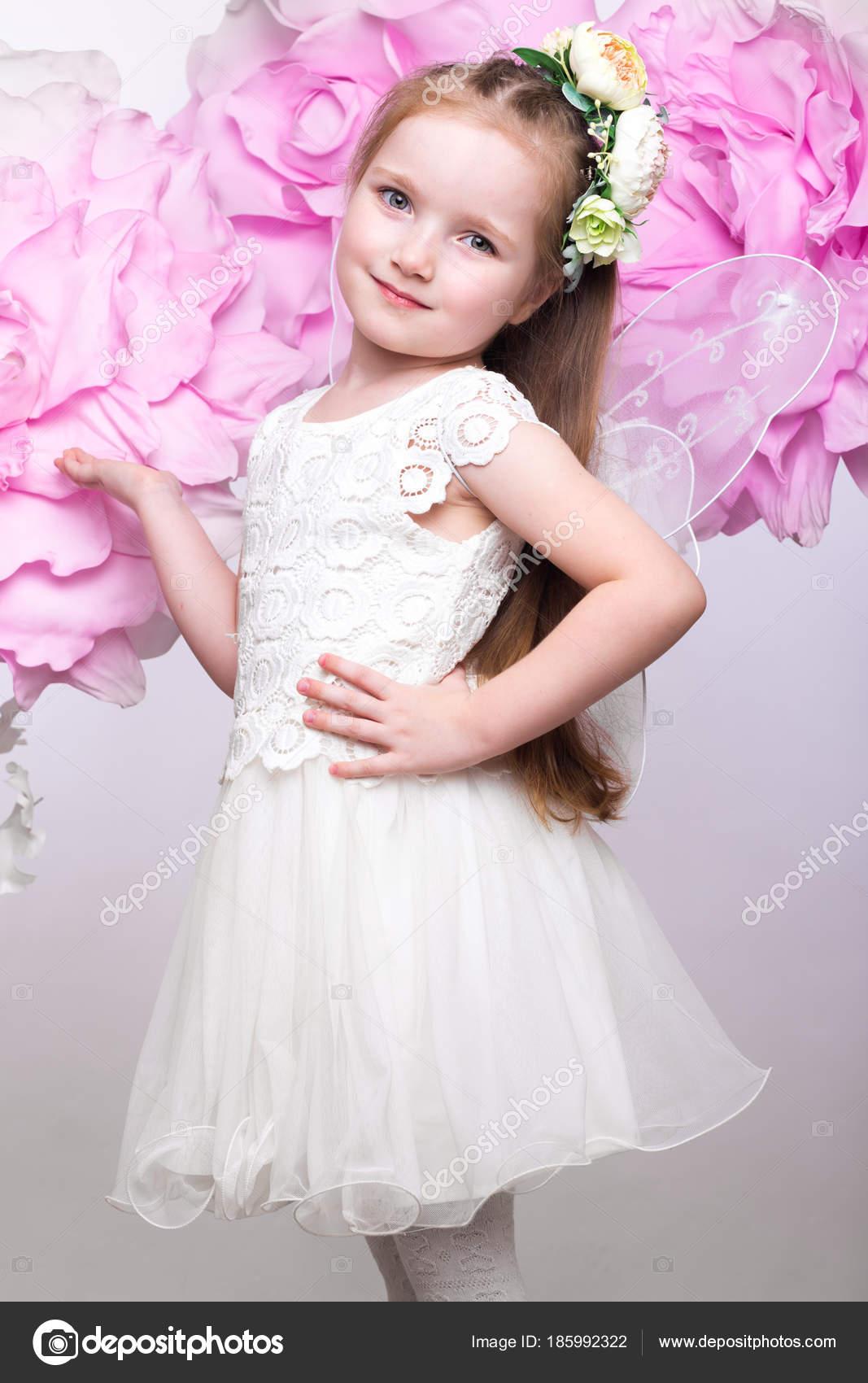 Niña hada con vestido blanco sobre un fondo de flores — Foto de ...