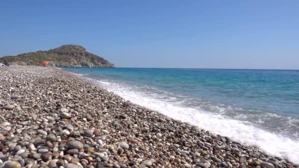 Afandou pláž, Pobřeží Středozemního moře, oblázková pláž, vlny, útes v pozadí, ostrov Rhodos Řecko.