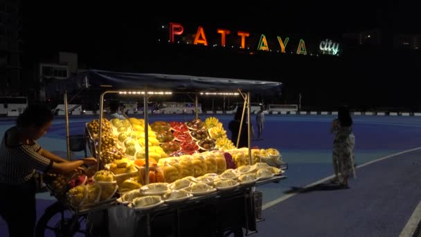 Pattaya, evening, mobile shopping tent with fruit, in the background glow big letters Pattaya city. Pattaya, Thailand 7.12.2017
