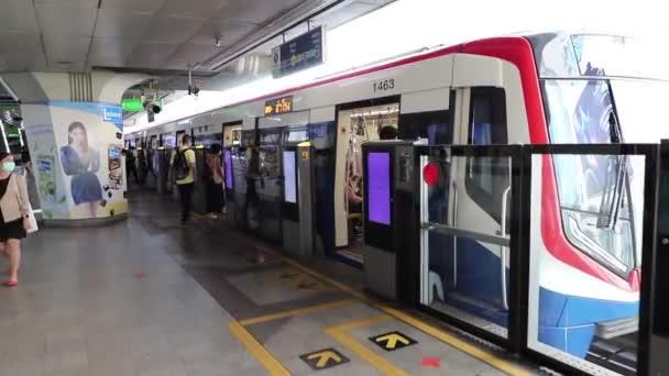 BTS Skytrain Bangkok cestující nastupují do vlaku a odjíždějí. Thajsko Bangkok březen 2020