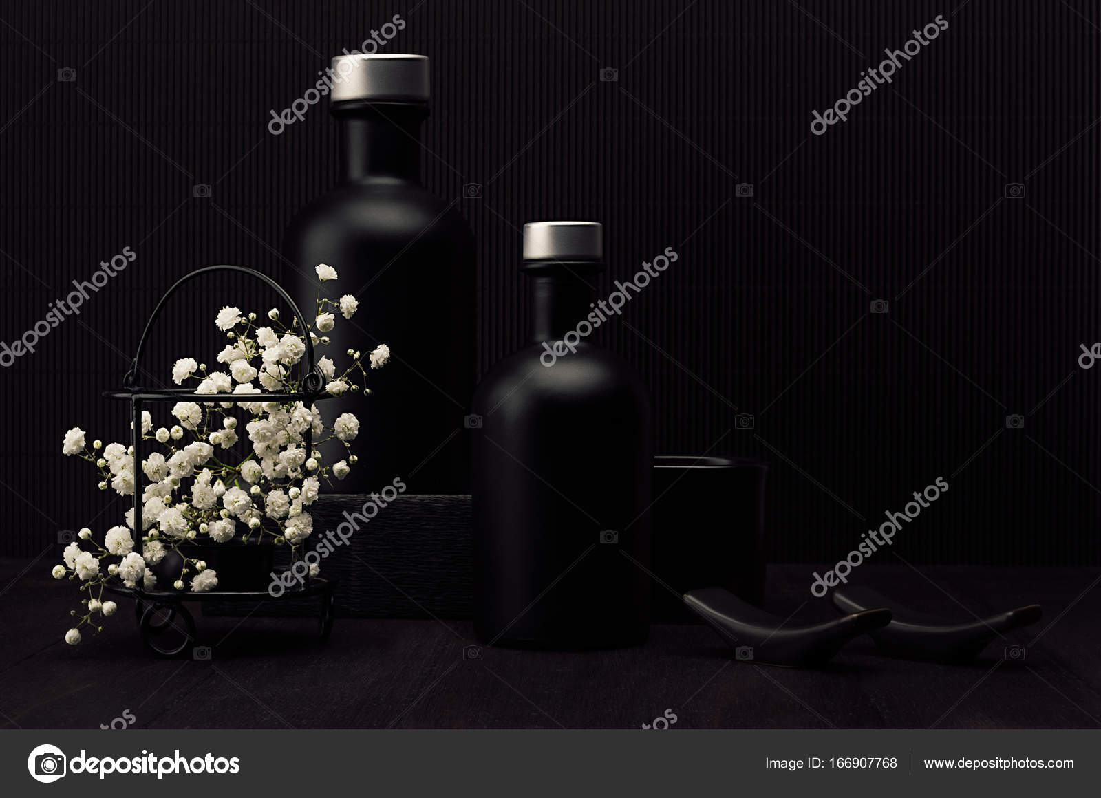 Exquisite Home Designers. Noir exquisite home decor with blank black cosmetics bottles  white small flowers on dark wood