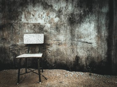 Small chair in front of dirty concrete wall with copy space