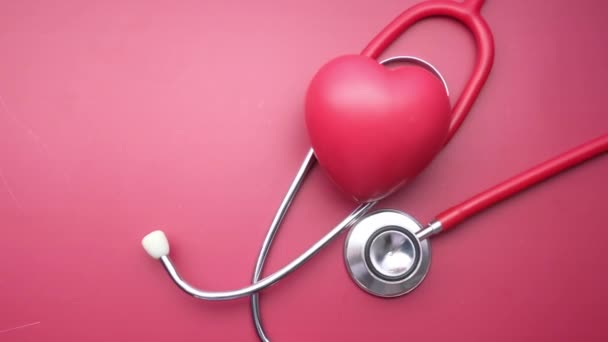 top view of heart shape and stethoscope on red background