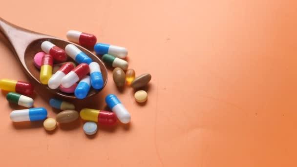 Multi bunte Pillen und Kapsel auf Löffel auf farbigem Hintergrund