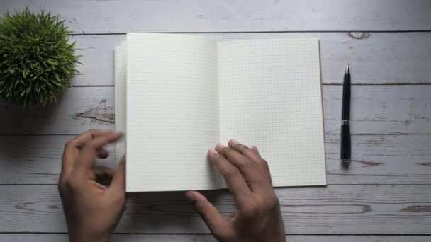 top view of man hand turning paper of notepad