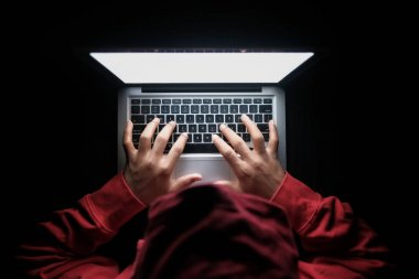 hooded hacker hand stealing data from laptop