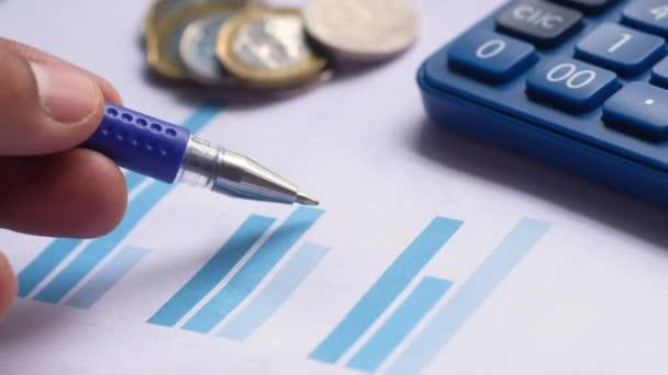mladý muž analyzující finanční údaje na papíře