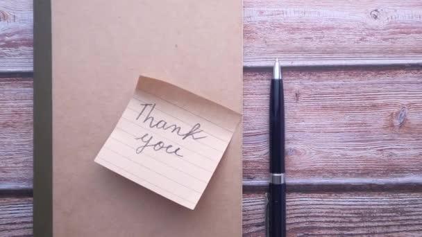 Dankeschön-Zettel und Stift auf dem Tisch