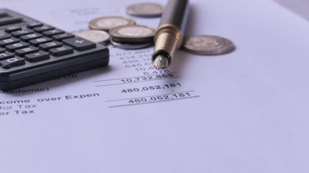 Close up of accounting figure, coin, pen on table