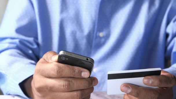 Mans Hände halten eine Kreditkarte mit Smartphone für Online-Einkäufe