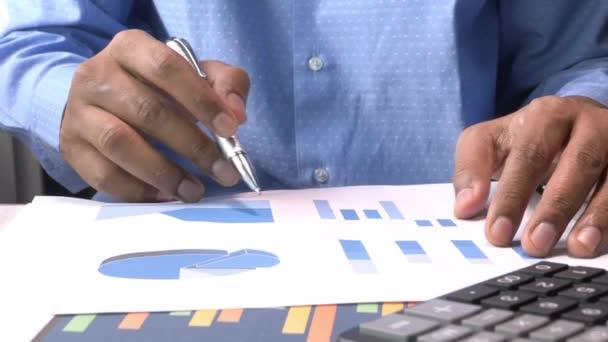 man hand analyzing financial chart on office desk