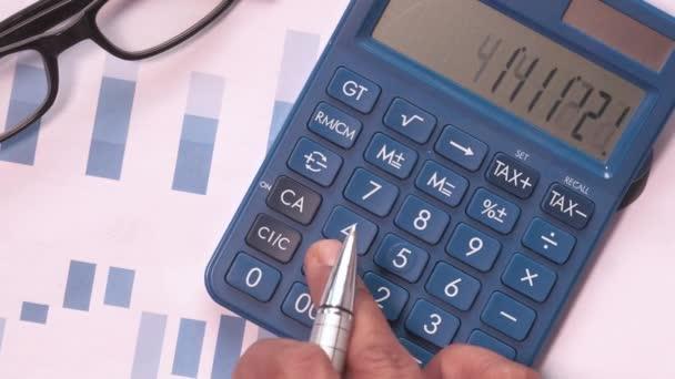 Detailní záběr rukou pomocí kalkulačky a finančního diagramu na stole
