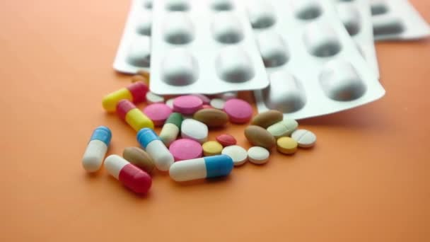 colorful pills and blister pack on orange background