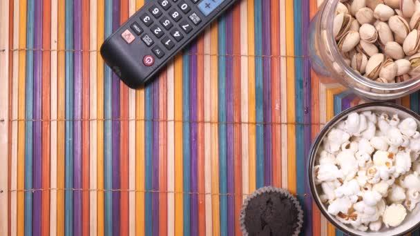 Zblízka chutné chipsy, popcorn, ořechy a TV dálkové na tabne