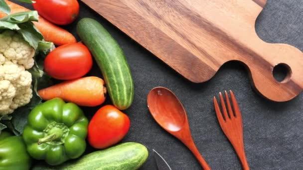 friss zöldség vágódeszkán villával és kanállal