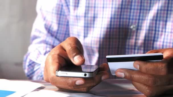 Mann mit Kreditkarte und Smartphone, Online-Shopping-Konzept
