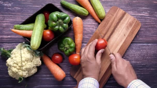 Pohled shora na člověka, jak krájí čerstvou zeleninu.