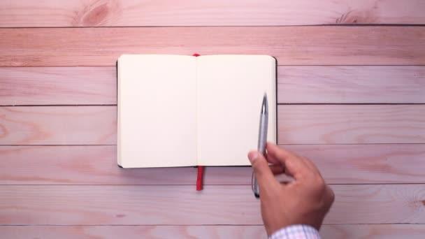 üzletasszony tesz toll nyitott jegyzettömb, felső nézet .