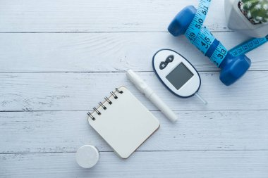blood sugar measurement kits for diabetes with dumbbell on table