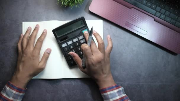 person hand using calculator and writing on notebook