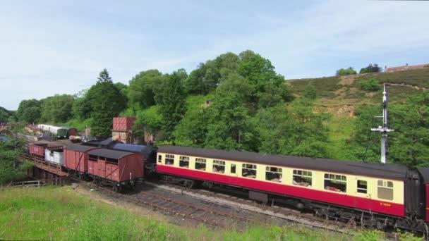 Na stanici Goathland přijíždí parní vlak. Stanice je na Severní Yorkshire Moors Railway v severní Anglii.