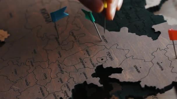 Ruka připíchnout červenou vlajku na zemi Číny. mapa světa v ruštině. Čínská města s barevnými kolíky na dřevěné mapě.Koncept cestování destinace, dovolená v Asii. Pushpin na hlavní město Pekingu.