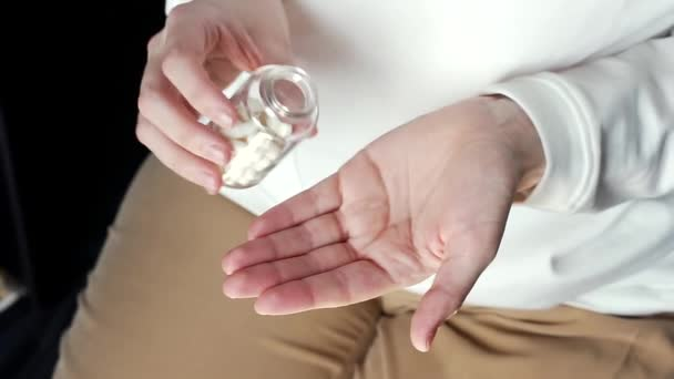 young adult woman taking medicine painkiller pills pouring on female hand capsules from meds bottle. health care, medicare, pharmacy and treatment concept, close up view.