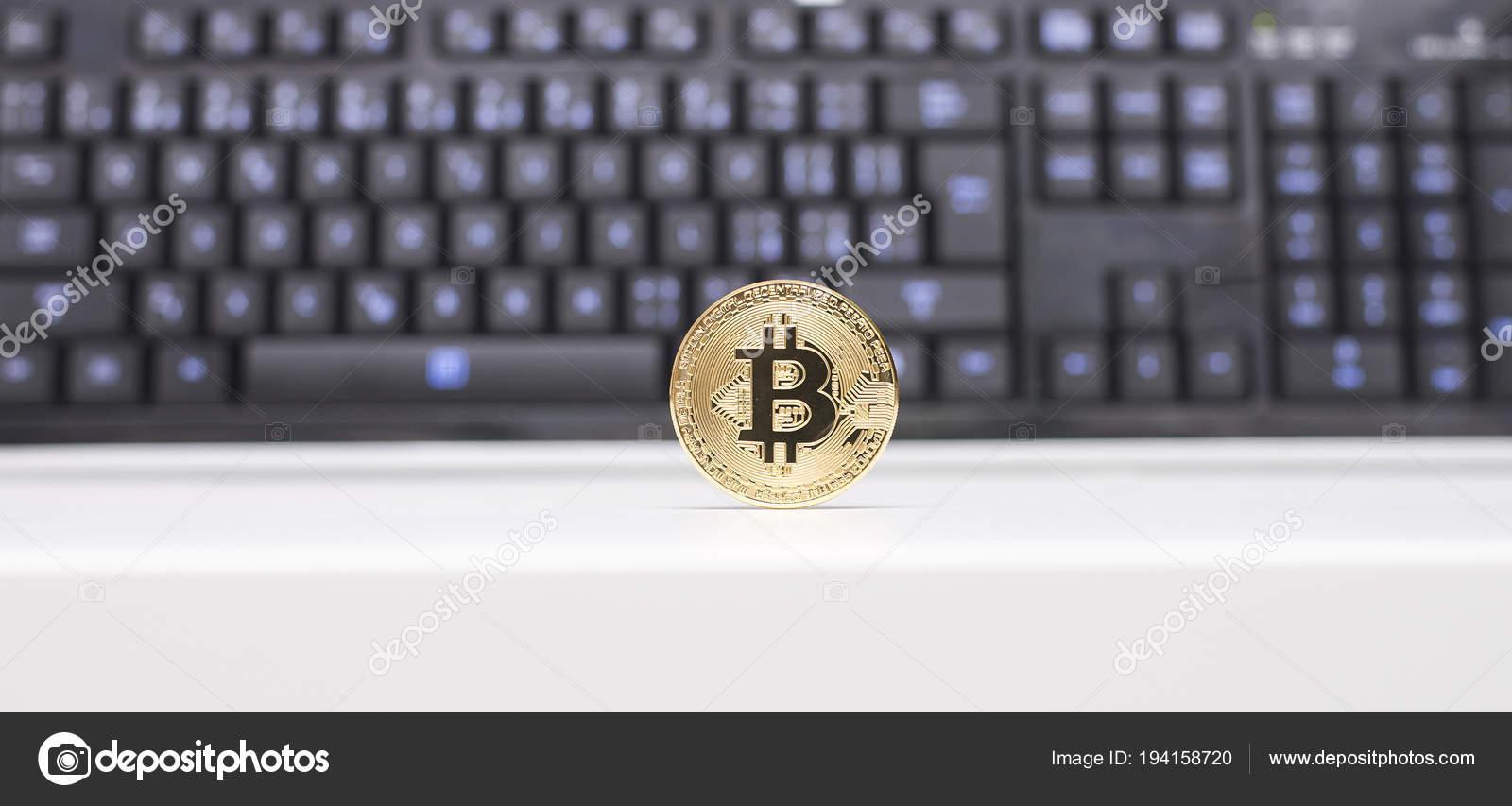Pièce bitcoin debout sur bureau blanc devant clavier noir avec