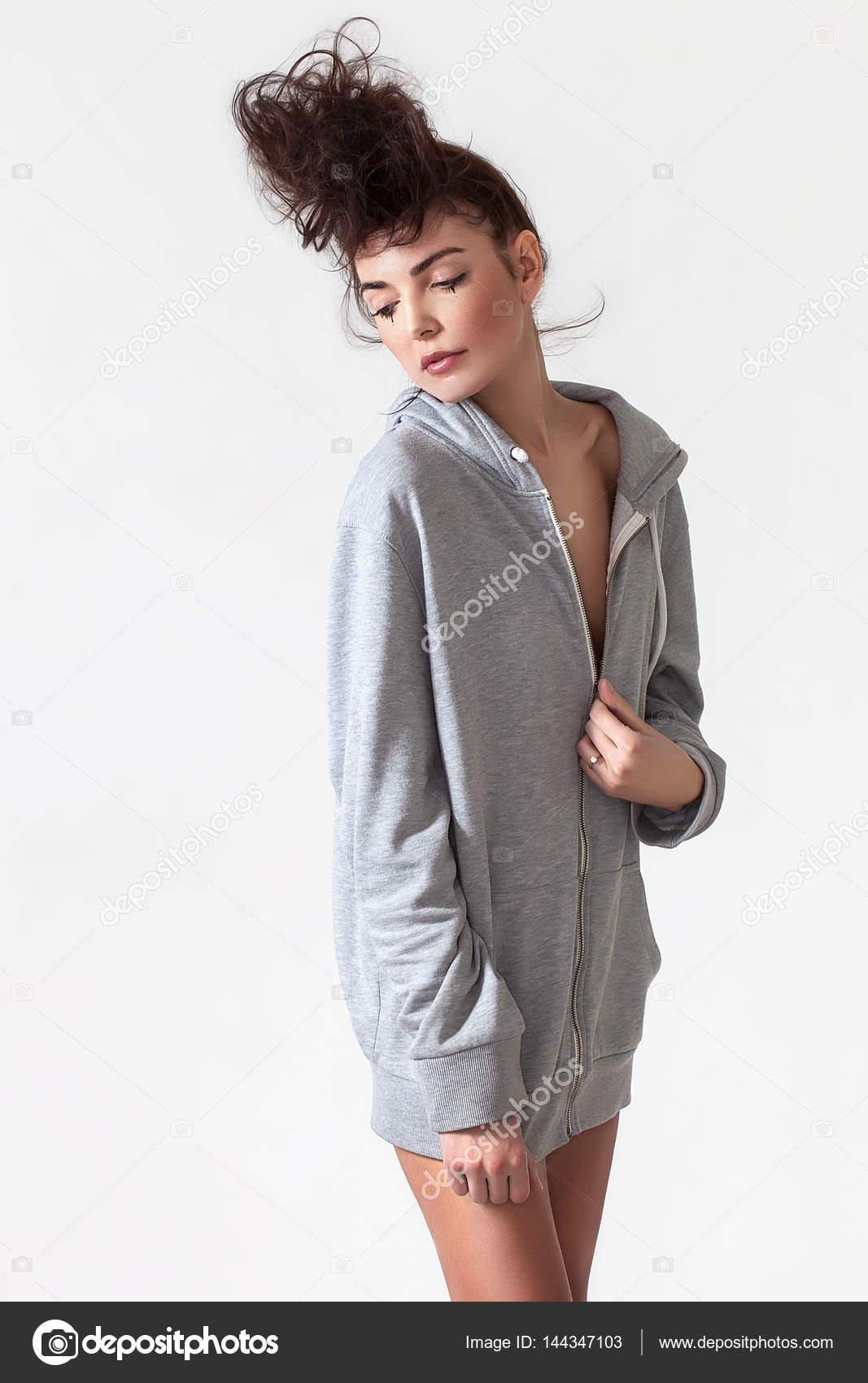 d18b6c234ae Beautiful woman with messy hair wearing grey hoodie and posing– stock image