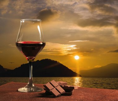Red wine glass with chocolate and beautiful sunset on Lake Iseo