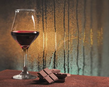 Red wine glass with chocolate and rainy windowpane