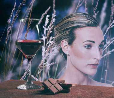 Red wine glass with chocolate and beautiful girl portrait with field