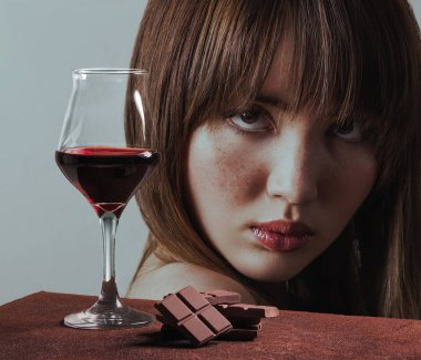Red wine glass with chocolate and beautiful girl with freckles