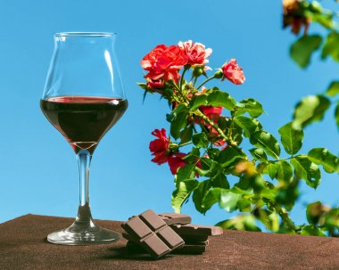 Wine glass with chocolate and beautiful red roses with blue sky