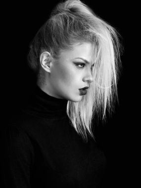 Blonde pretty girl profile portrait on black background, monochrome