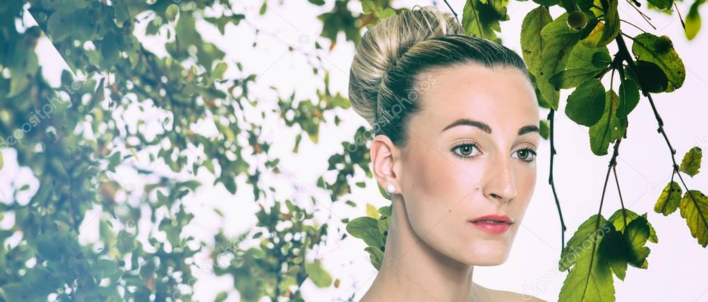 Blonde pretty girl portrait with hair bun and green leaves, letterbox
