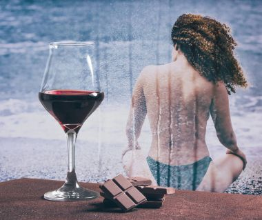 Red wine with chocolate and woman sitting on the beach with rain on glass