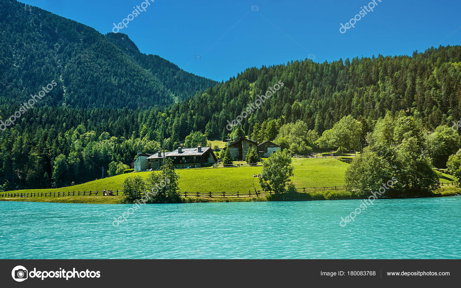 Pine Woods Cottages And Beautiful Blue Lake In North Italy Mountains Stock Photo