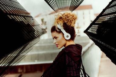 Double exposure of sporty woman portrait listening to music and skyscrapers