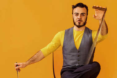 Man portrait sitting on chair and holding musical saw
