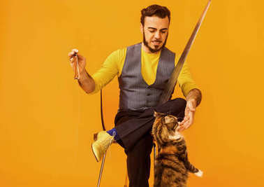 Man portrait sitting on chair while holding musical saw and petting cat