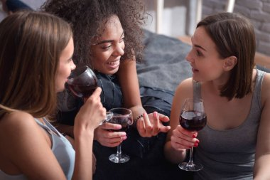 Amused girls drinking wine and having exciting conversation