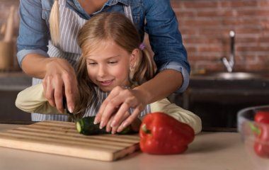Happy involved girl cutting a cucumber with her mother